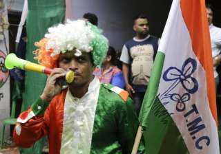 A supporter of All India Trinamool Congress party dressed in party colors celebrate after winning the West Bengal state assembly election, in Kolkata, India.
