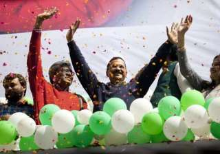 Leader of the Aam Aadmi Party, Arvind Kejriwal, center, waves to the crowd as his party looks set for a landslide party in New Delhi.