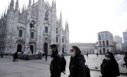 People wearing sanitary masks walk past the Duomo Gothic