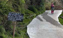 A sign at the entrance of a village reads 'Outsiders aren't