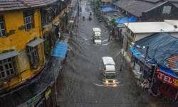 Mumbai: Vehicles ply on a waterlogged street during heavy rains, at Byculla area in Mumbai, Wednesda