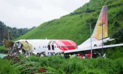 Officials stand on the debris of the Air India Express flight that skidded off a runway while landin