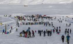 Indian tourists and locals ski on a slope in Gulmarg,
