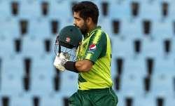 Pakistan's captain Babar Azam raises his helmet to