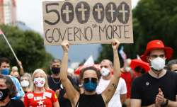 A woman wearing a face mask holds a sign with a message