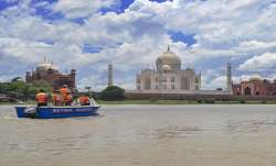 Police personnel patrol at the swollen Yamuna River in the